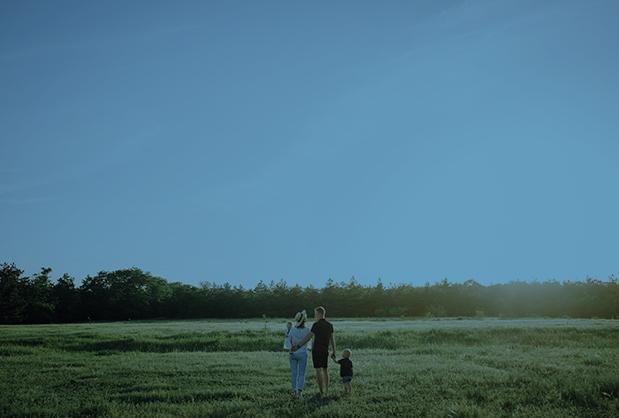 Family walking across a meadow.