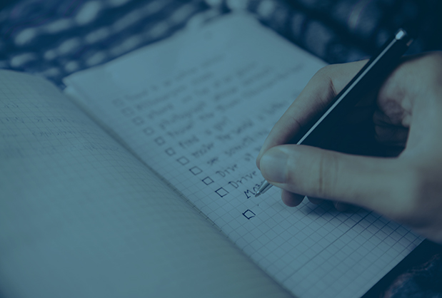 Person writing out checklist in a notebook.