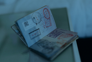 Open passport with colorful travel stamps in it.