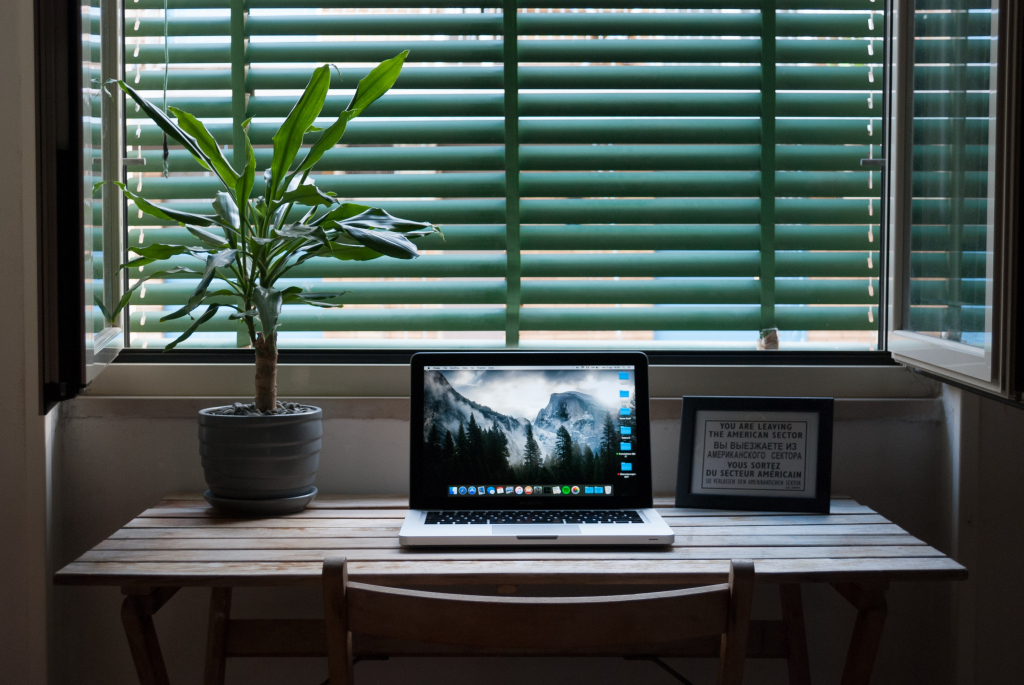 Clear Horizontal Surfaces Section Image. Photo of a clean desk with a plant and laptop.