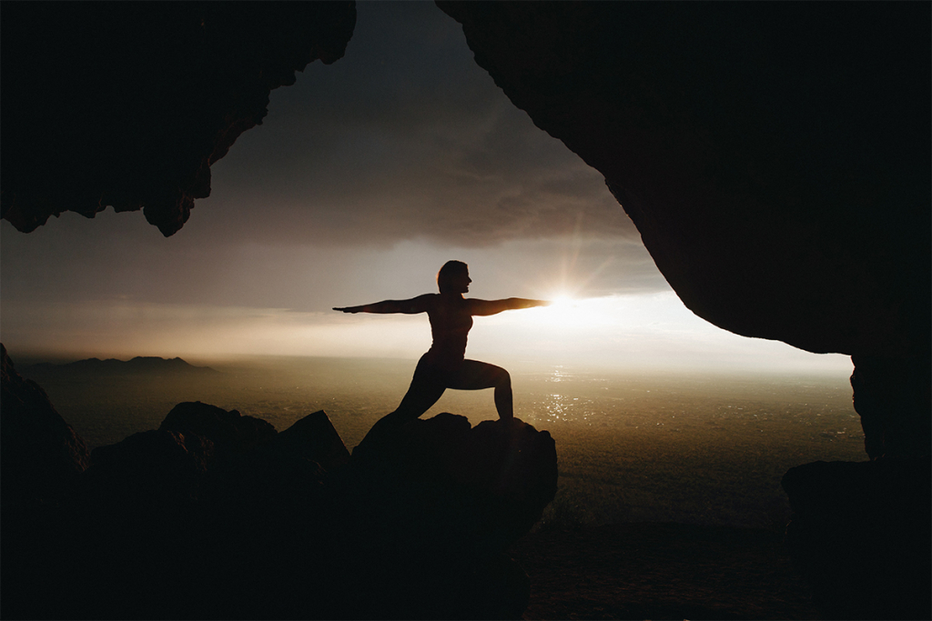 Silhouette of a person doing yoga with a sunrise in the background.