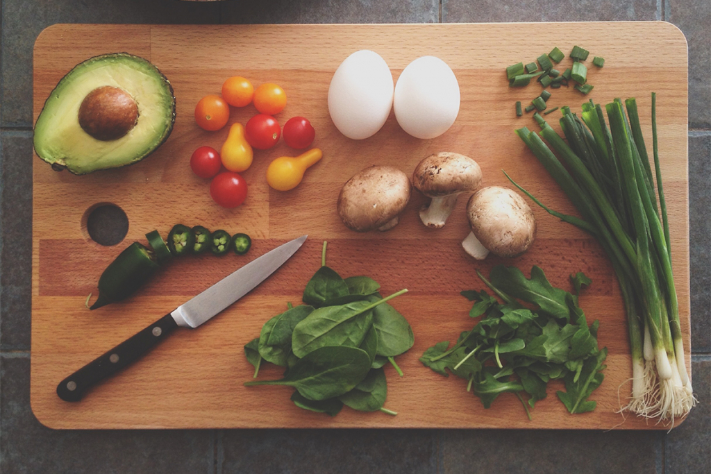 Image of cutting board with a knife and vegetables.