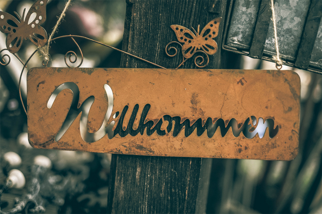 "Photo of Rustic Sign with ""Willkommen"" on it."
