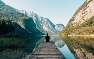 Photo of Person sitting on a dock looking out onto a lake and mountains by Simon Migaj on Unsplash