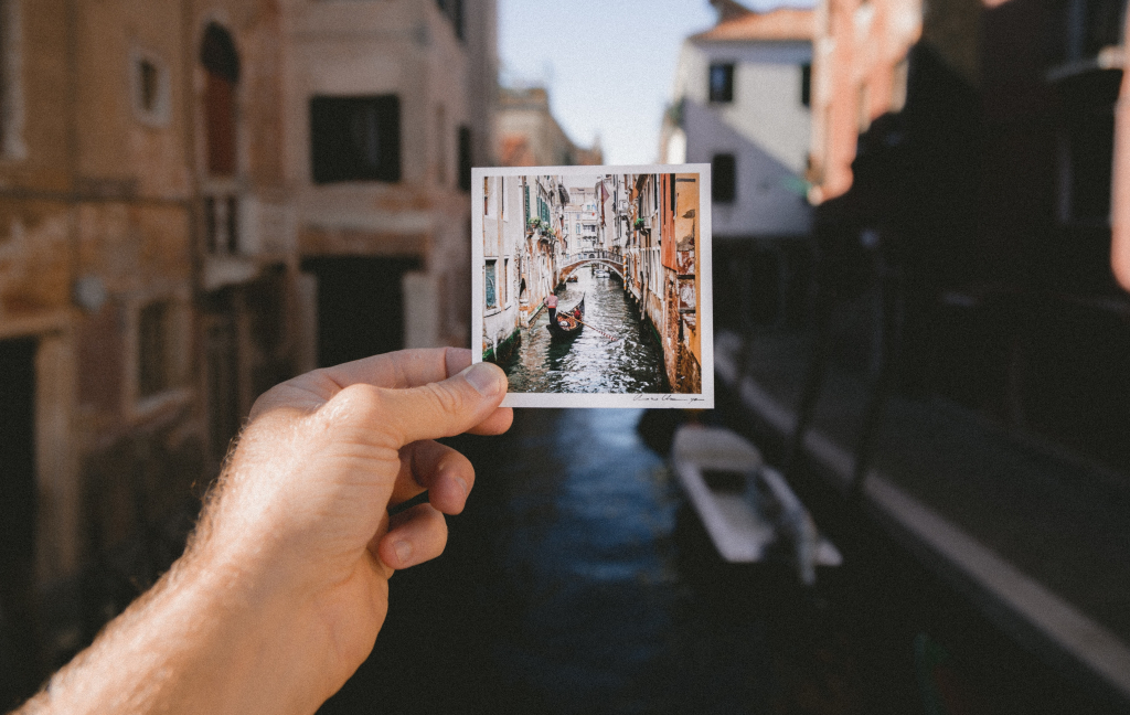 Basic Italian Phrases To Help You Get Around section image. Photo of man holding postcard in Italy.