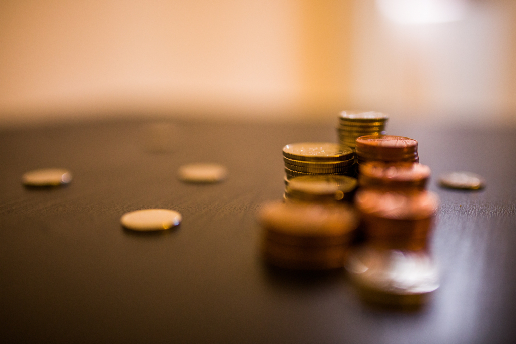 How are you funding your travels Image- Photo of coins on table.
