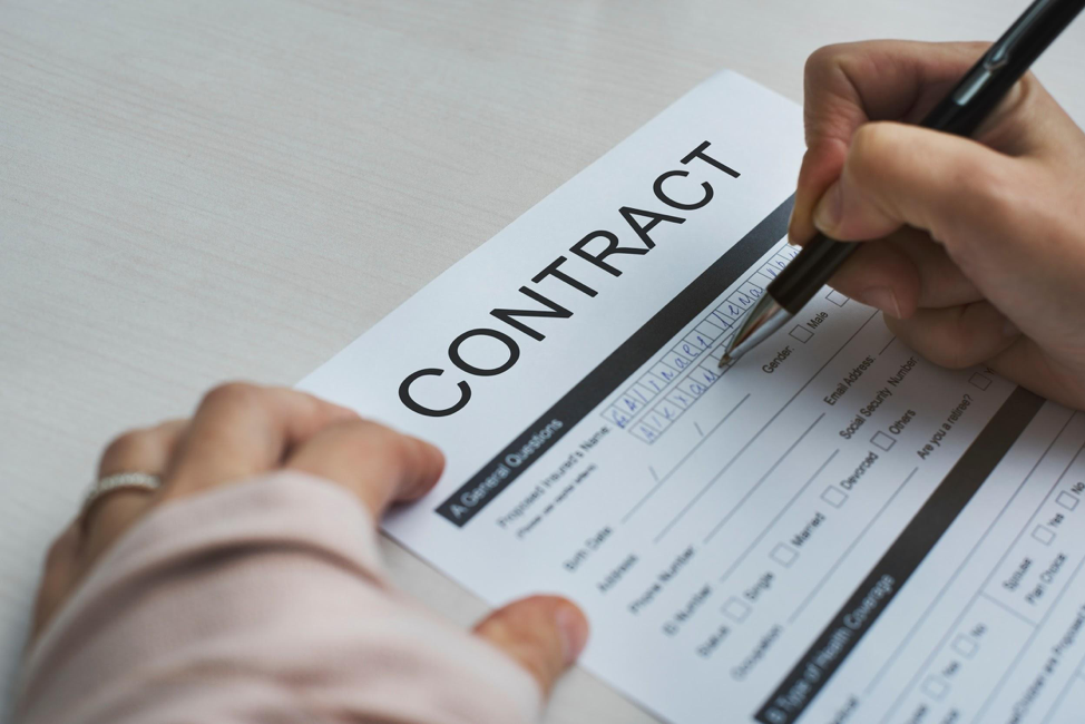 Picture of a person's hands signing a contract
