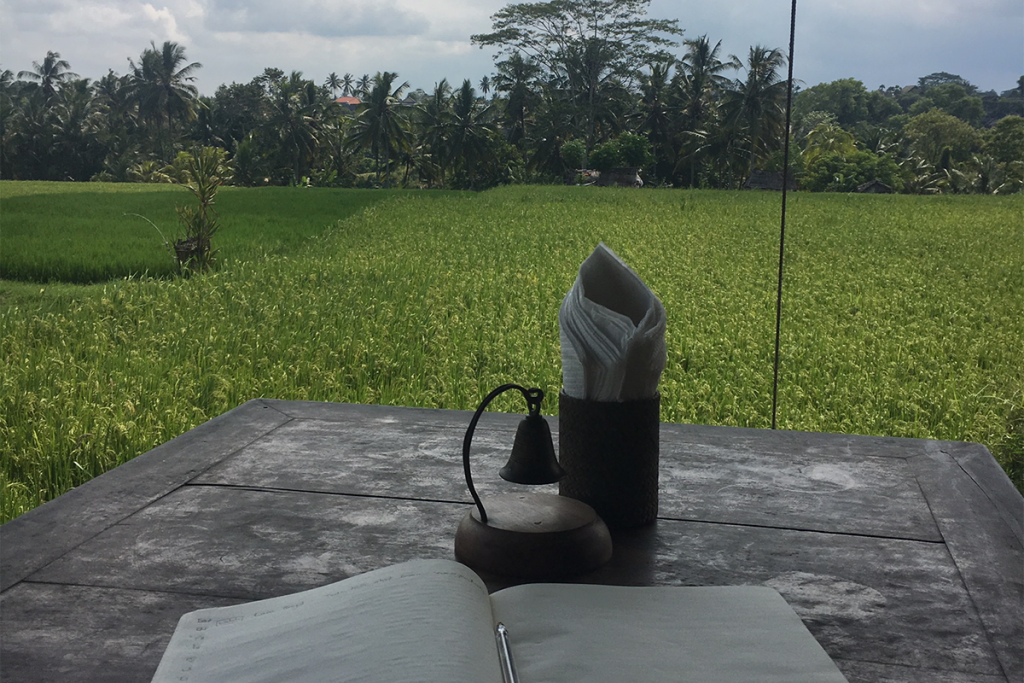 Rustic table and notebook looking out on a field in Bali.