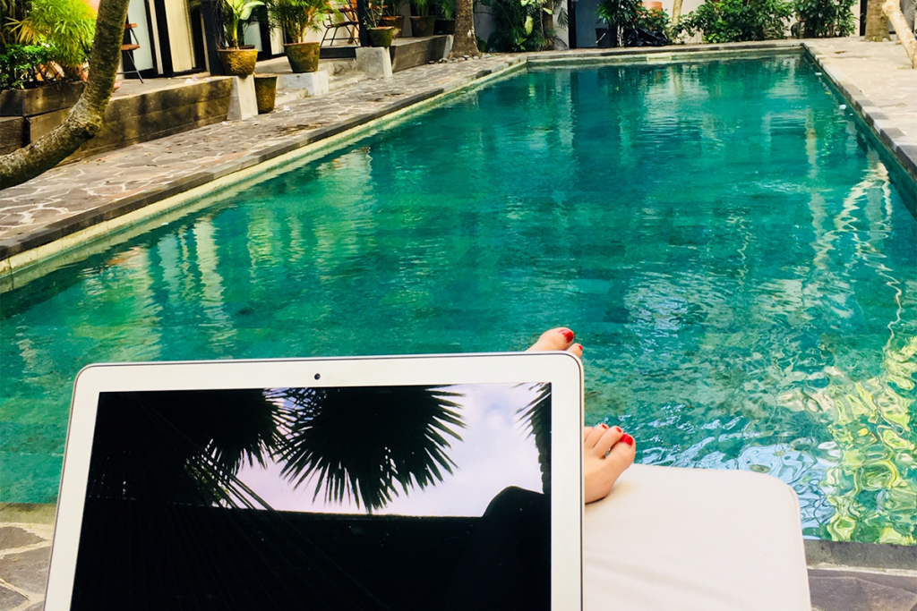 Photo of a person living the sabbatical life, working on a laptop with a view of a beautiful pool.
