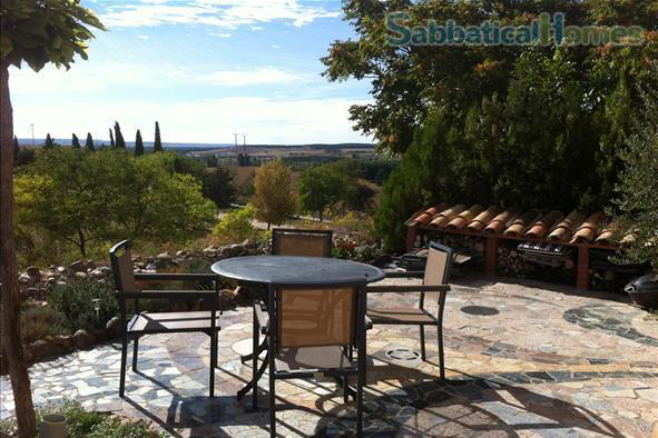 Image of an outdoor stone patio with a table overlooking the Spanish countryside.