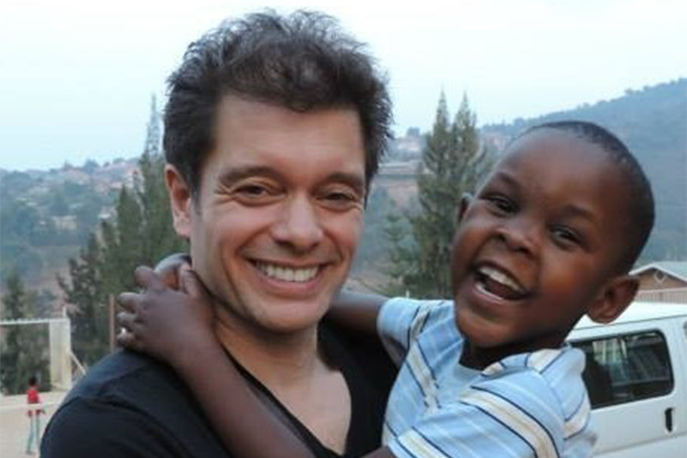 Image of Michael Stromme with a child he helps in Uganda.