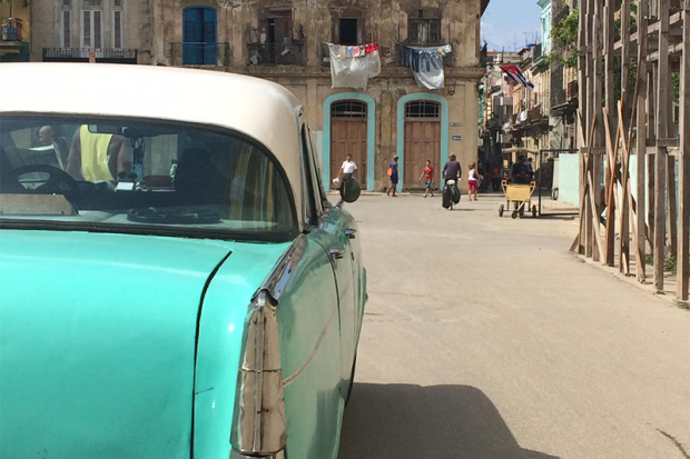 Image of a turquoise 1950's car on a street in Havana, Cuba