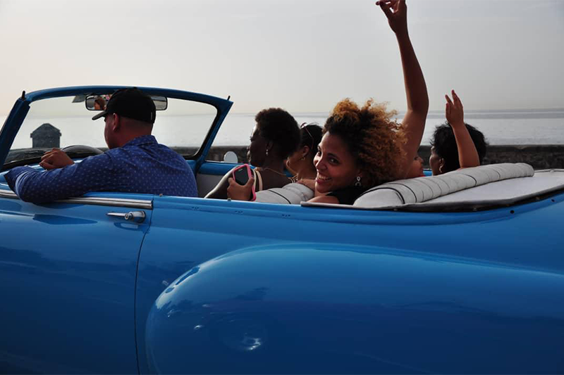 Picture of a group of people having fun in a convertible 1950's car in Havana, Cuba.