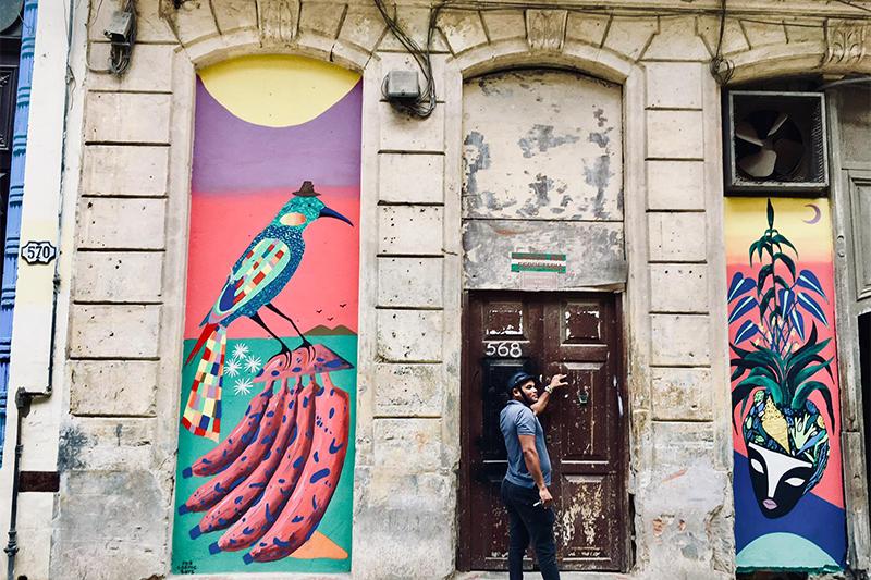 Image of a man in Havana, Cuba in front of a doorway with colorful artwork on either side of the door.